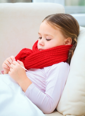 Ill little girl is reading thermometer while laying on sofa Stock Photo - 17412174