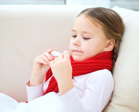 Ill little girl is reading thermometer while laying on sofa Stock Photo - 17412083