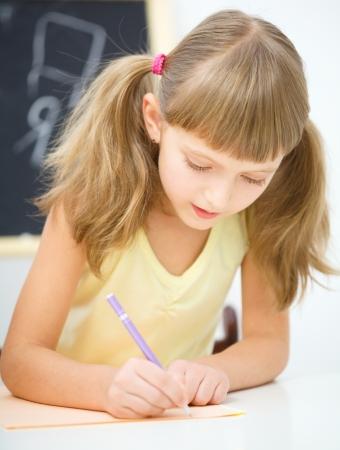 kids writing: Cute little girl is writing using a pen in preschool Stock Photo