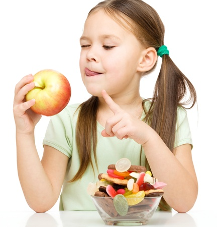 Cute little girl choosing between apples and sweets licking her lips, isolated over white Imagens - 17411981