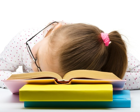 drowse: Cute little girl is sleeping on her books, isolated over white