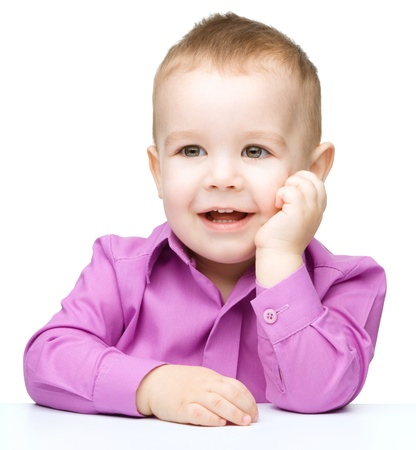 Portrait of a cute little boy sitting at table supporting his head with hands, isolated over white photo