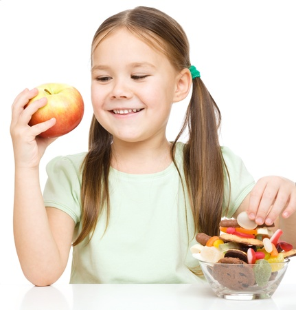 Cute little girl choosing between apples and sweets, isolated over white photo