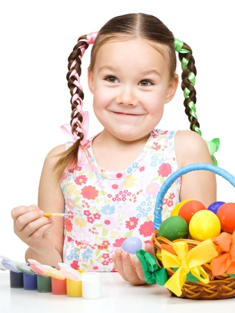 Little girl is painting eggs preparing for Easter, isolated over white photo
