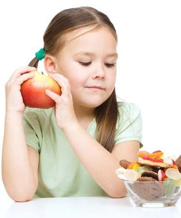 unhealthy eating: Cute little girl choosing between apples and sweets, isolated over white Stock Photo