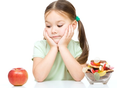 Cute little girl choosing between apples and sweets, isolated over white Stock Photo