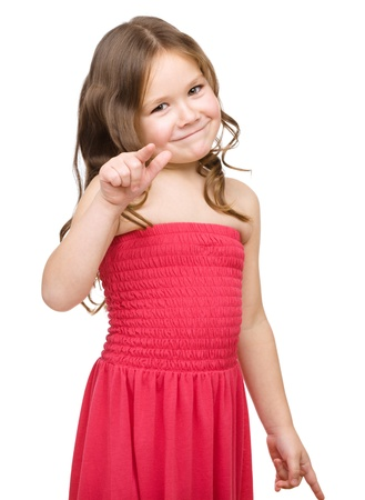 little finger: Fashion portrait of a cute little girl in red dress pointing her finger on you, isolated over white Stock Photo