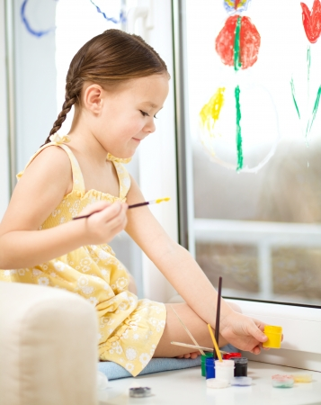 Portrait of a cute cheerful girl playing with paints on window Stock Photo - 17576732