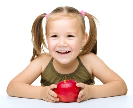 Portrait of a cute cheerful little girl with red apple, isolated over white photo