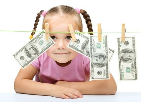 La niña linda está jugando con papel moneda - dólares, aislado más de blanco
