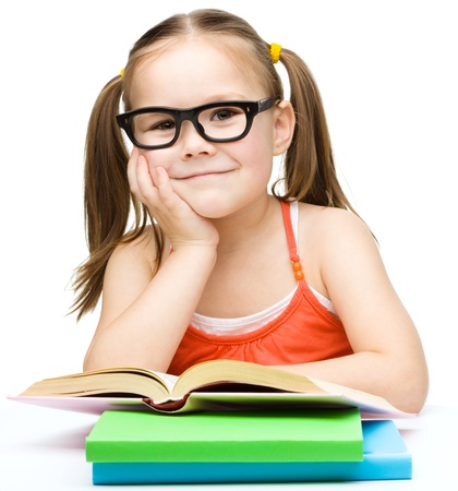 Cute little girl is reading a book while wearing glasses, isolated over white Banque d'images