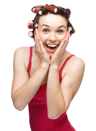 exhilarated: Young woman is holding her face in astonishment while wearing hair-rollers, isolated over white