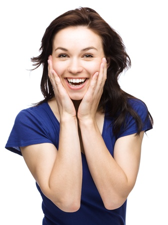Young woman is holding her face in astonishment, isolated over white Stock Photo