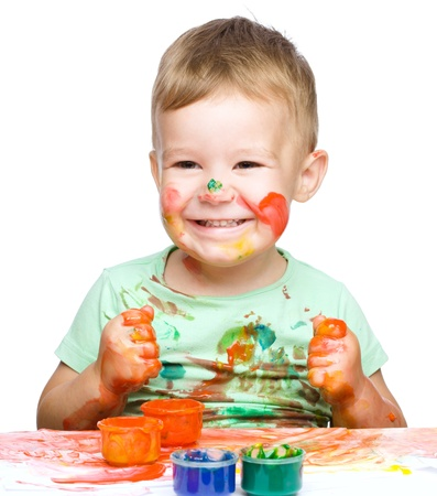 Portrait of a cute little boy playing with paints clenching his fists in joy, isolated over white photo