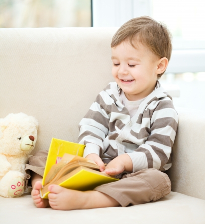 one story: Little boy is reading book while sitting on couch, indoor shoot