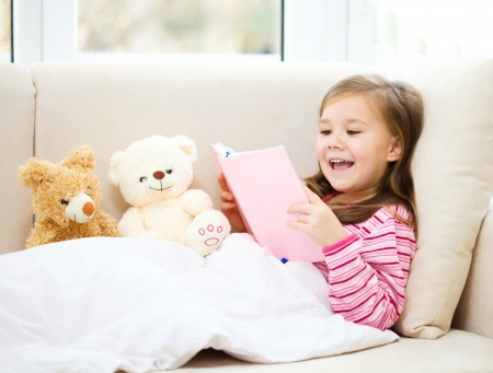 Little girl is reading a story for her teddy bears while laying in bed and wearing pajama, indoor shoot Imagens