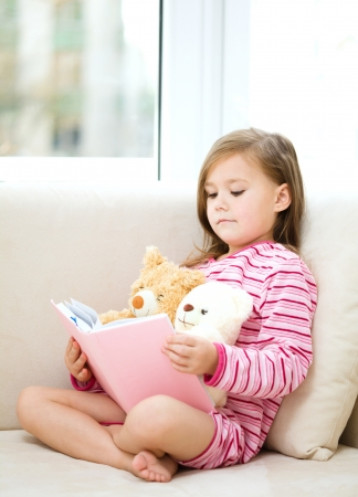 in pajama: Little girl is reading a story for her teddy bears while laying in bed and wearing pajama, indoor shoot Stock Photo