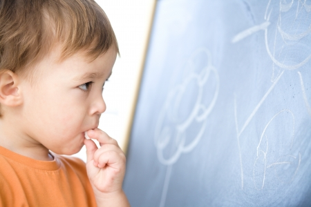 Little boy is biting chalk while looking at a blackboard in preschool, isolated over white photo