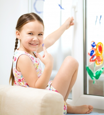 Portrait of a cute cheerful girl playing with paints on window Stock Photo - 17886726
