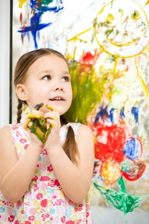 fingerpaint: Portrait of a cute cheerful girl showing her painted hands