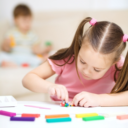 art and craft: Little girl is playing with plasticine, her mother and brother at the background Stock Photo