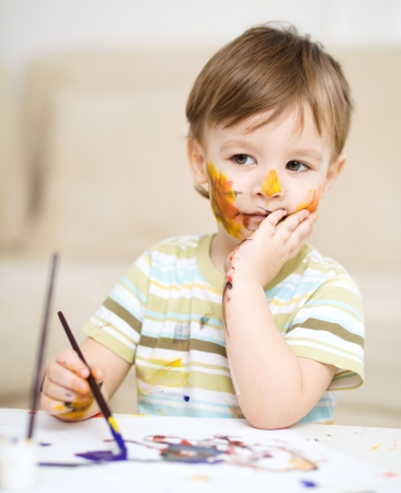 messily: Portrait of a sad little boy messily playing with paints