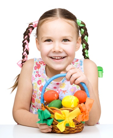 Little girl with basket full of colorful eggs preparing for Easter, isolated over white photo