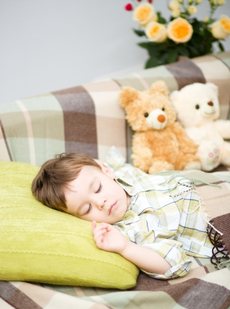 Cute little boy is sleeping next to his teddy bears Stock Photo - 17886588