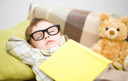 Cute little boy is sleeping in front of his teddy bears wearing glasses and put off a big book Stock Photo - 17886745