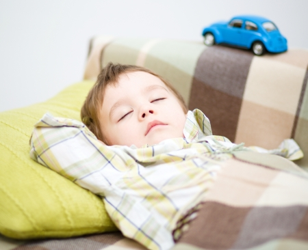 snooze: Cute little boy is sleeping in front of his car toy