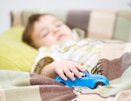 dream car: Niño lindo está durmiendo mientras mantiene su coche de juguete Foto de archivo