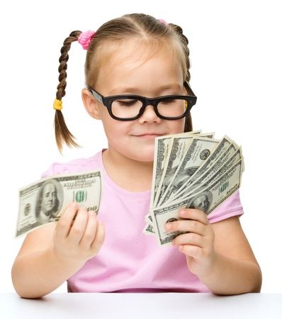 Cute little girl is counting dollars, isolated over white photo