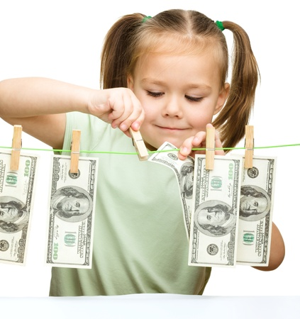 Cute little girl is playing with paper money - dollars, isolated over white photo
