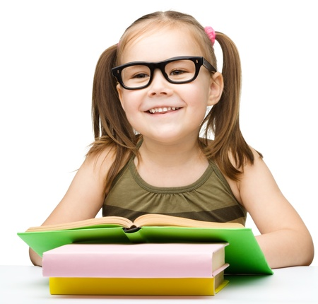 Cute little girl is reading a book while wearing glasses, isolated over white photo