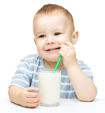 Cute little boy drinks milk using a drinking straw, isolated over white photo