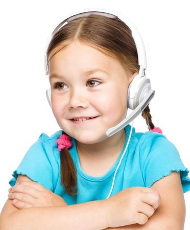 niÑos hablando: Chica joven linda está trabajando como un operador en línea de ayuda hablar con los clientes utilizando auriculares, aislado más de blanco