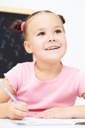 Cute little girl is writing using a pen in preschool photo