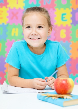 Cute little girl is writing using a pen Stock Photo - 18441386
