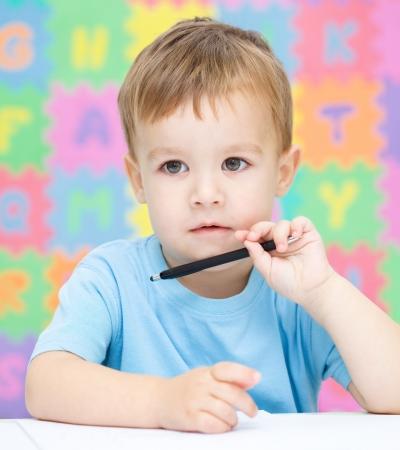 preschool classroom: Little boy is writing on his copybook in preschool