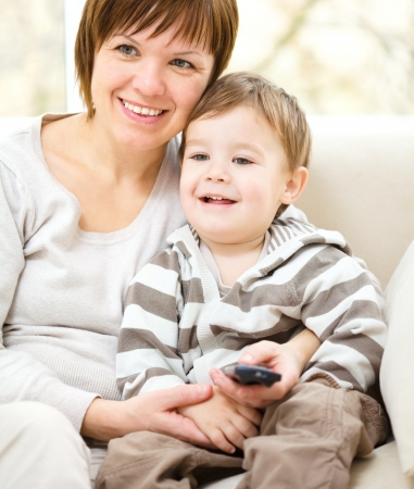 Mother and her son are watching tv while sitting on a couch photo