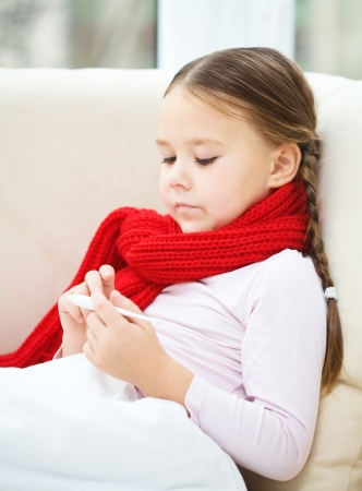 Ill little girl is reading thermometer while laying on sofa Stock Photo - 18441353