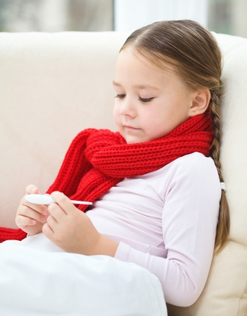 Ill little girl is reading thermometer while laying on sofa Stock Photo - 18441354