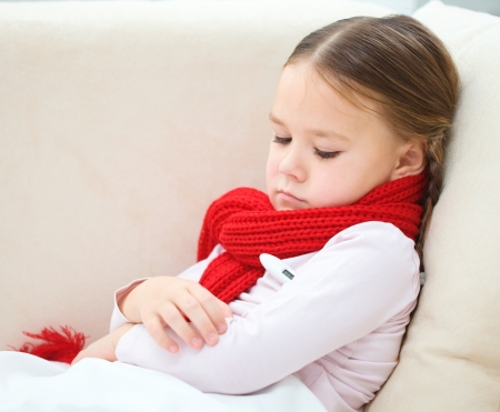 Ill little girl is laying on sofa with thermometer under her arm Stock Photo - 18441290
