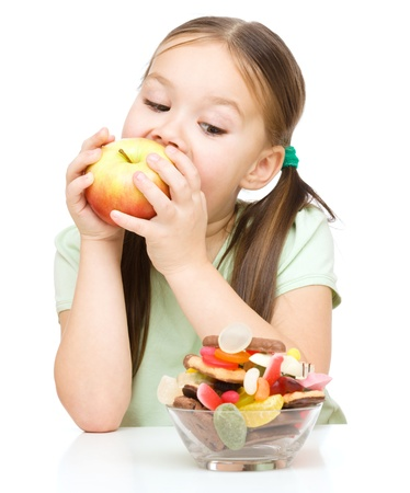 Cute little girl choosing between apples and sweets, isolated over white Imagens
