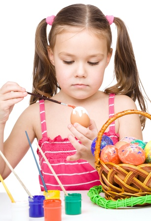Little girl is painting eggs preparing for Easter, isolated over white Stock Photo - 18441396