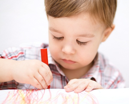 daycare: Little boy is drawing on white paper using crayon Stock Photo