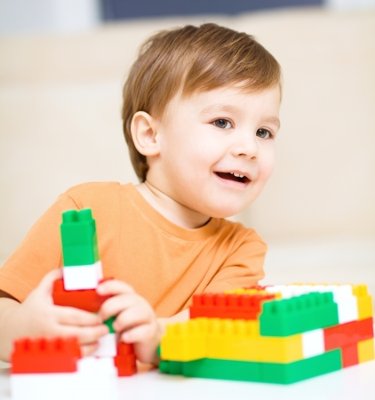Cute little boy is playing with building blocks photo