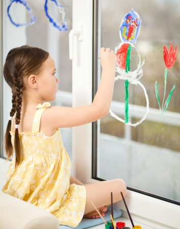 fingerpaint: Portrait of a cute cheerful girl playing with paints on window
