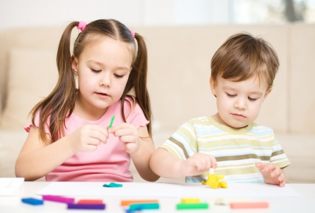 the color of silence: Little sister and brother are playing with plasticine
