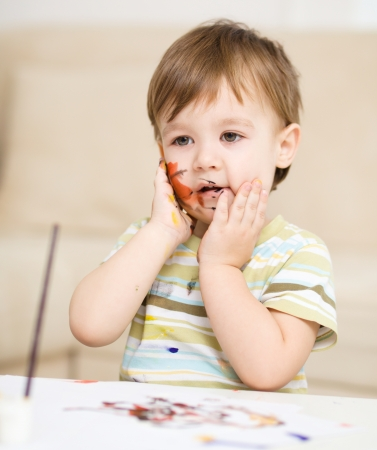 messily: Portrait of a cute little boy messily playing with paints